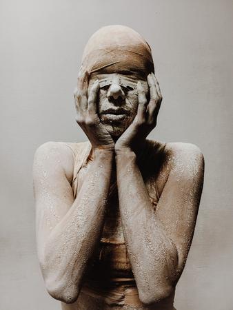 en el maquillaje, una mujer con vendas y arcilla es como una momia sin ojos sobre un fondo monofónico. Tema de Halloween Foto de archivo