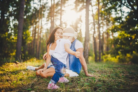 young parents are taught to walk a daughter of one year on nature in a park on a lawn. The first steps of the childs hand with his mother and father. Stock Photo