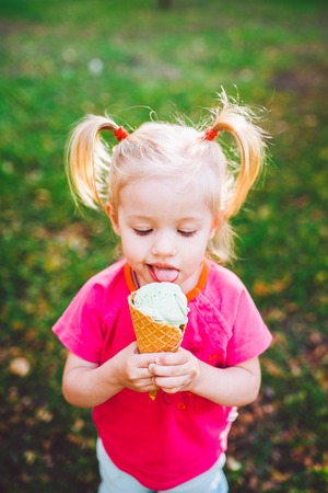 little funny Caucasian girl blonde with blue eyes with two tails on head eating an ice cream in a waffle cup of blue sitting on green grass.All face dirty in melted ice cream.Looks down at the camera. Stock Photo