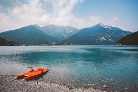Italy view of a mountain lake lago di ledro with a beach and a lifeboat catamaran of red color in summer in cloudy weather. Banco de Imagens - 92907882