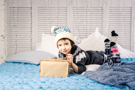little girl the child sitting in pajamas and hat on the bed with garland of light bulbs with gifts boxes wrapped in a non-colored paper decorated with cones on blue knitted coverlet.Christmas concept.