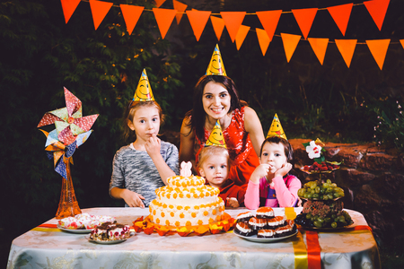 a large mother and three children at a festive table with sweets and a cake in the courtyard decorated with lights and a garland of lamps. The concept of a family childrens birthday party.