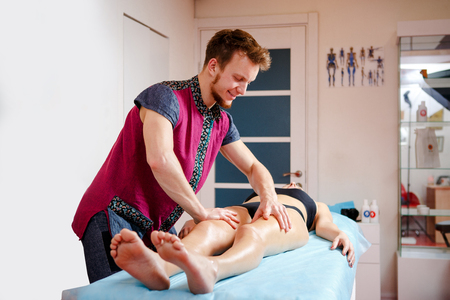 The concept of massage and health. A young male massage therapist does lymphatic drainage and massage for the muscle tone of a girl in black underwear on a table in a physiological room. Stock Photo