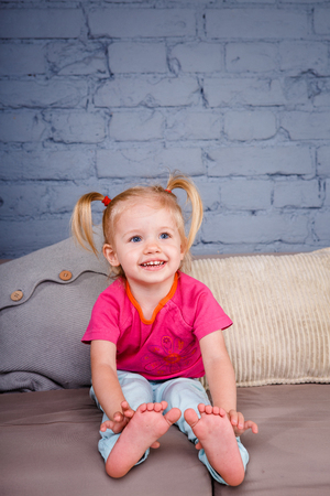 the little funny girl indulges on the sofa at home with her hands behind her heels. He laughs showing his tongue and teeth. Dressed in bright stylish clothes.