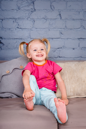 the little funny girl indulges on the sofa at home with her hands behind her heels. Stock Photo