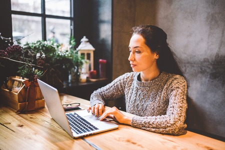 beautiful young brunette woman using a laptop at coffee shop at a wooden table near window typing text on a keyboard. In winter, with the light from the lamp, she is dressed in a warm gray sweater. 版權商用圖片