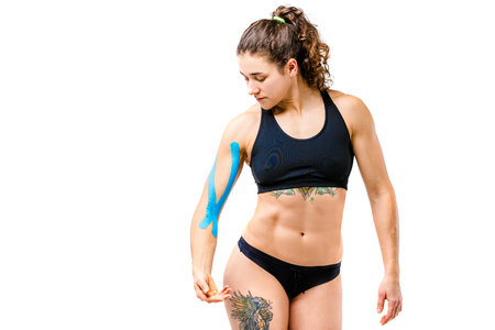 Concept of sports medicine and health. A young cowish girl with a good figure posing on a white isolated background with a kinesiology tape, a sticky blue ribbon on her arm. Alternative medicine.