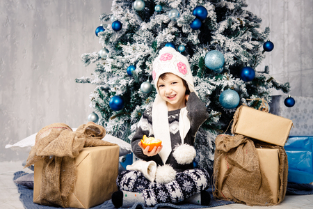Little girl child of five years sitting on the floor near Christmas tree decorated with toys, balls. In the hands holds an orange fruit tangerine, orange. dressed in a funny folder and a gray sweater.