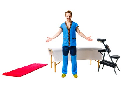 male masseur in blue uniform stands with gesture of greeting hands to the sides with smile next to equipment for massage