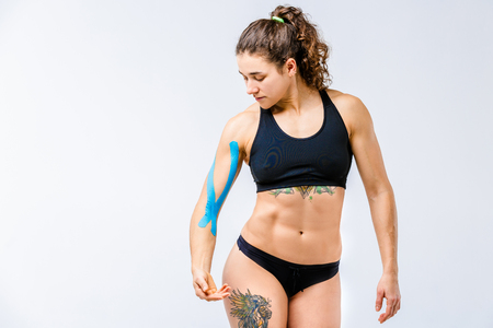 Concept of sports medicine and health. beautiful girl with good figure posing on gray background with kinesiology tape,a sticky blue ribbon on her arm.Alternative medicine for stretching and pain.