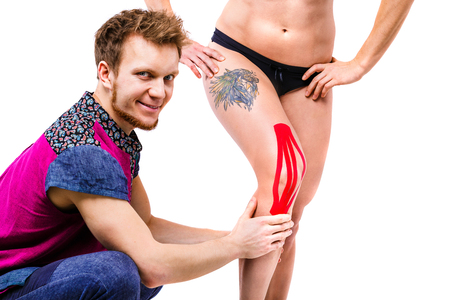 young doctor the therapist sets on the knee a beautiful strong with a good figure of the patient kinesiology tape of red color.The concept of sports medicine and recovery from injuries.Tattoo on thigh