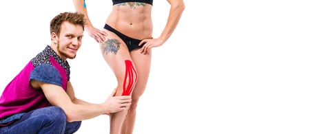 young doctor the therapist sets on a knee beautiful with a good figure of a patient kinesiology tape of red color. The concept of sports medicine and recovery from injuries. Banner and space for text.
