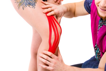 close-up, hands the doctor the therapist sets on a knee with a good figure of the patient kinesiology tape. Concept of sports medicine and recovery after trauma.Whole isolated background.