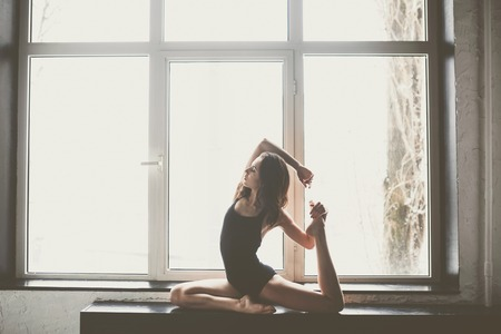 beautiful girl dancer with long flowing hair in black clothes, swimsuit,in a beautiful beautiful pose on the big window Daylight, silhouette of a beautiful body.Dance theme Contemporary and Classical.