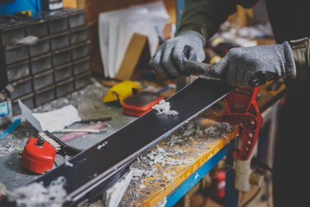 A male worker in a ski service workshop repairs the sliding surface of the skis. Close-up of a hand with a plastic scrapper for removing wax, removing new wax. Theme repair of ski curb. Banco de Imagens