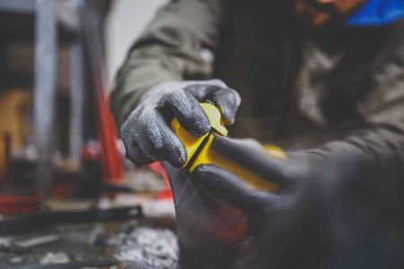 Trabajador de sexo masculino que repara la piedra, afilado de bordes en el taller de servicios de esquí, superficie deslizante de los esquís. El afilado de los bordes de los esquís de montaña por medio de la herramienta individual. Reparación temática del bordillo. Foto de archivo - 94194021