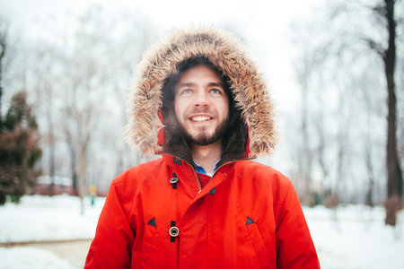 Portrait, close-up of young stylishly man smiling with a beard dressed in red winter jacket with a hood and fur on his head stands against the background of a snow-covered city. Winter and frost theme Stock Photo