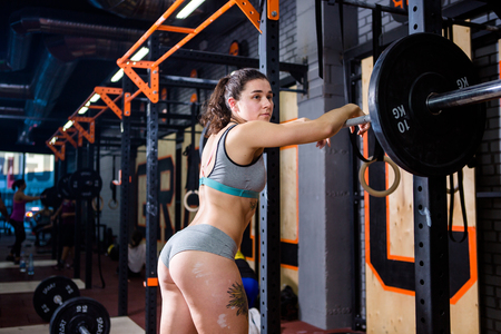 Crossfit and sport theme. beautiful sexy girl with bare booty in a bikini and Tshirt stands tired near the bar and rests after training with heavy weight. Deadlift and training of leg and back muscles Stockfoto