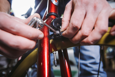 Theme repair bikes. Close-up of a Caucasian mans hand use a hand tool hexagon set to adjust and install Rim Brakes on a red bicycle.