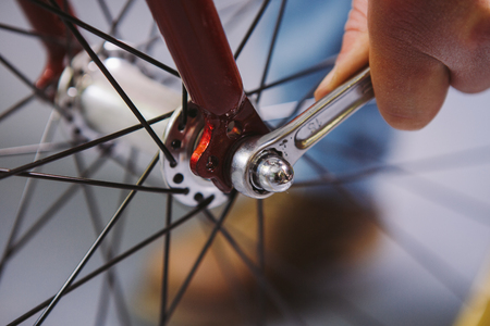Theme repair bikes. Close-up of a Caucasian mans hand use a hand tool Bike Tools Hub Cone Wrenc to adjust and install Quick Releases and Thru Axles on a red bicycle.