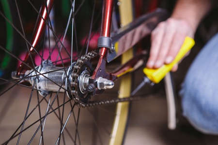 Theme repair bikes. Close-up of a Caucasian mans hand use a Chain Lubricant in a yellow lubricator for llubricator a bicycle chain on a red bicycle.