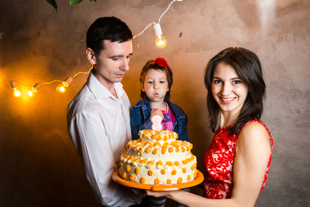 Theme family holiday childrens birthday and blowing out candles on large cake. young family of three people standing and holding 5 year old daughter in yard against gray wall and garland yellow bulbs.