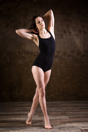 A very thin young girl, full-length with her long, flowing hair, is standing in a black swimsuit on a dark brown wooden background. Weight problems with anorexia nervosa.