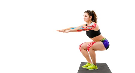 Theme kinesiology tape rehabilitation and health of athletes. Beautiful girl doing a squat exercise on a black rug on a white isolated background. On the arm and knee, a sticky colored ribbon. Stock Photo
