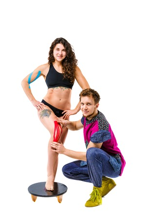 Beautiful girl stands on a white background, male therapist doctor glues a colored tape to stabilize the muscles and tendon on the knee. Stock Photo