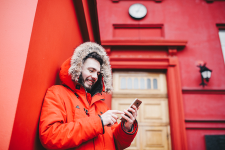 A handsome young guy with beard and red jacket in hood a student uses a mobile phone, writes, writes a correspondence over the phone with a smile against the red building of the university or college.