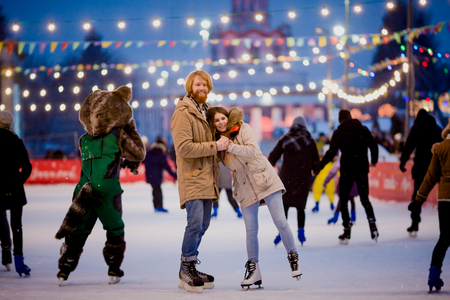 Ice skating rink and lovers together. A pair of young, stylish people in an embrace in a crowd on a city skating rink lit by light bulbs and bright lights. Winter date for Christmas on the ice arena