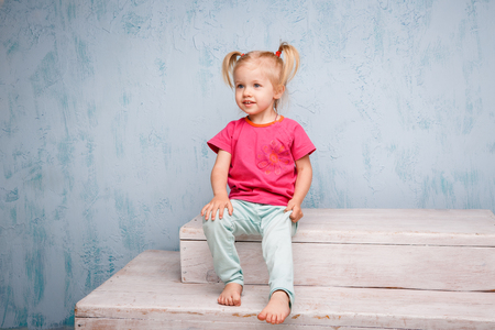 Little funny blue-eyed girl child blonde with a haircut two ponytails on her head sitting on a gossip on the background of an old textured wall in blue. Dressed in stylish bright clothes.
