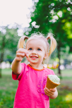 little funny girl blonde eating sweet blue ice cream in a waffle cup on a green summer background in the park. smeared her face and cheeks and laughs. Dressed in bright stylish clothes.