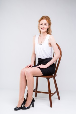 Portrait of beautiful business woman with long red, curly hair sitting on wooden chair on white background in studio. Dressed in a white blouse with a short sleeve and black short skirt and high heels Stockfoto