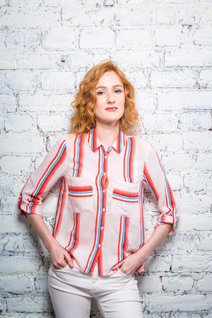 A beautiful young woman student with red curly hair and freckles is leaning against a brick wall of gray color. Dressed in a red striped shirt and white pants.