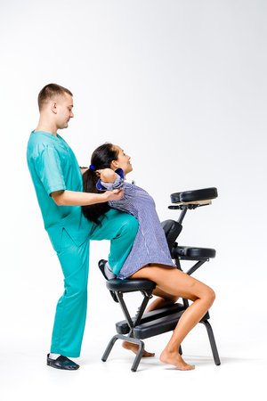 Theme massage and office. young male therapist in blue suit doing back massage with his knee braced in the spine of female worker, business woman in shirt on shiatsu massage chair for fatigue relief.