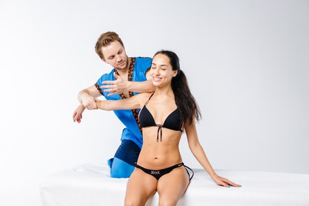 Theme massage and body care. Young doctor masseur in working suit makes massage to relax and strengthen the muscles of the neck, shoulder and hands of beautiful girl sitting on table in black lingerie Stock Photo
