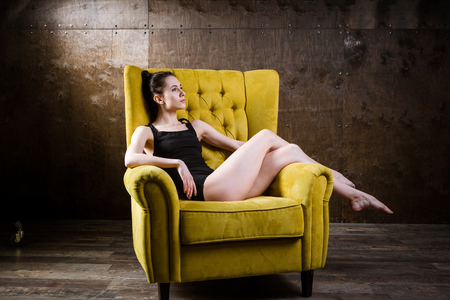 A young beautiful, sexy Caucasian woman with thin figure and long bare legs, barefoot posing reclining on yellow armchair in the interior against dark wooden wall. Dressed in a black classic swimsuit.