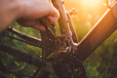hand with a bicycle tool was engaged in fixing a bicycle outdoors at sunset close-up