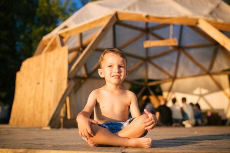 Theme is yoga and children. Caucasian Boy child sitting barefoot cross-legged in lotus position on wooden floor the background of gathering place of people. In summer sunset. Dressed in denim shorts. Stock Photo