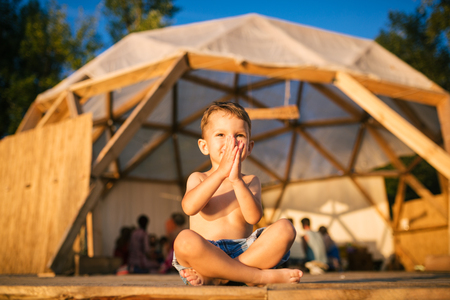 Theme yoga and children. Caucasian Boy in blue shorts child sits barefoot with his legs crossed in lotus pose and waving his arms with smile on wooden floor against the gathering place. In the summer.