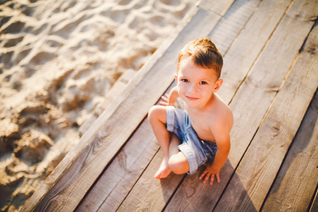 The theme is a child and summer beach vacation. A small Caucasian boy sits sideways on a wooden pier and looks at the camera on a sandy beach and a pond, a river. With bare legs in blue denim shorts. Stock Photo