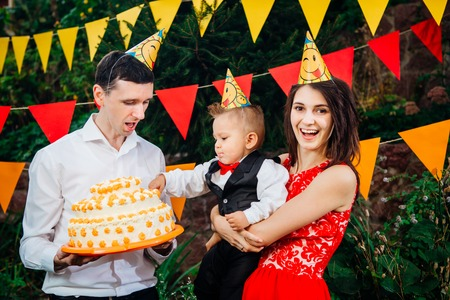 Subject childrens birthday party, food and sweets. A young family celebrates one year of son. Dad is holding a big cake, mom is holding a baby in her arms. Baby tastes finger cream on cake with cake. Stock Photo
