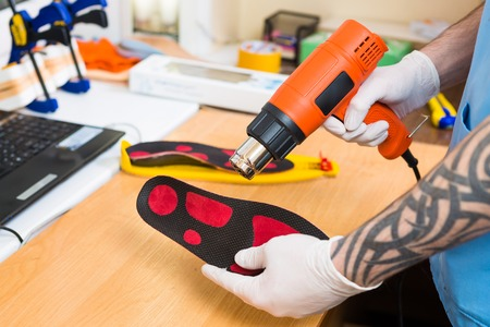 closeup Hands of young man with tattoo in workshop dressed in blue uniform make individual orthopedic insoles. The instrument uses hairdryer to heat and deform. Theme of small business and medicine.