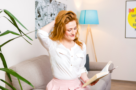 Beautiful young woman student with long red hair in pink skirt and shirt reading book, holding in hand textbook sitting on sofa home, in light interior against floor lamp and picture. Next house plant Stock Photo