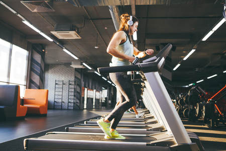 Beautiful young woman with long hair trains in the gym on a treadmill. Listens to music in large headphones. On his arm a sports watch in black for tracking speed, heart rate, pace and stopwatch.
