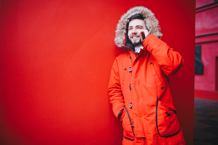 handsome young male student with a toothy smile and a beard stands on a red wall background in a bright red winter jacket with a hood with fur in winter. Uses a mobile phone, talk and call. Banco de Imagens