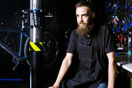 Portrait of small business owner of young man with beard. Guy bicycle mechanic workshop worker sitting with tool in his hand in a working black clothes in an apron in the background of a bicycle shop. Stock Photo