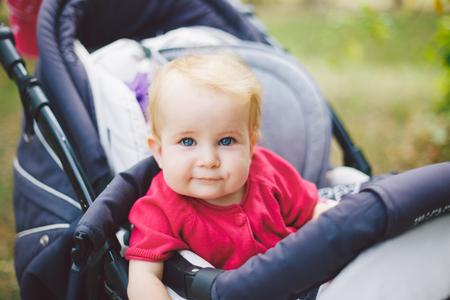 Ritratto di una piccola ragazza bionda divertente del bambino con gli occhi azzurri che si siede in un passeggino di bambino in estate per i verdi. Trinasport per bambino e trasporto bambini a un anno dalla nascita.