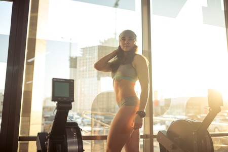 Beautiful sexy Caucasian woman of nationality with perfect and tattooed figure in seductive sportswear Panties and bra posing standing near window in gym near rowing simulator.